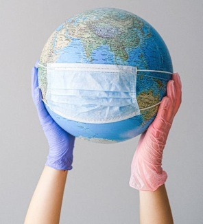 Face mask over a globe symbolizes the COVID-19 pandemic
